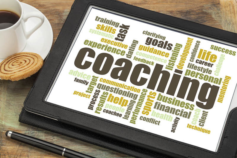 coaching concept - a related word cloud on a digital tablet with cup of coffee